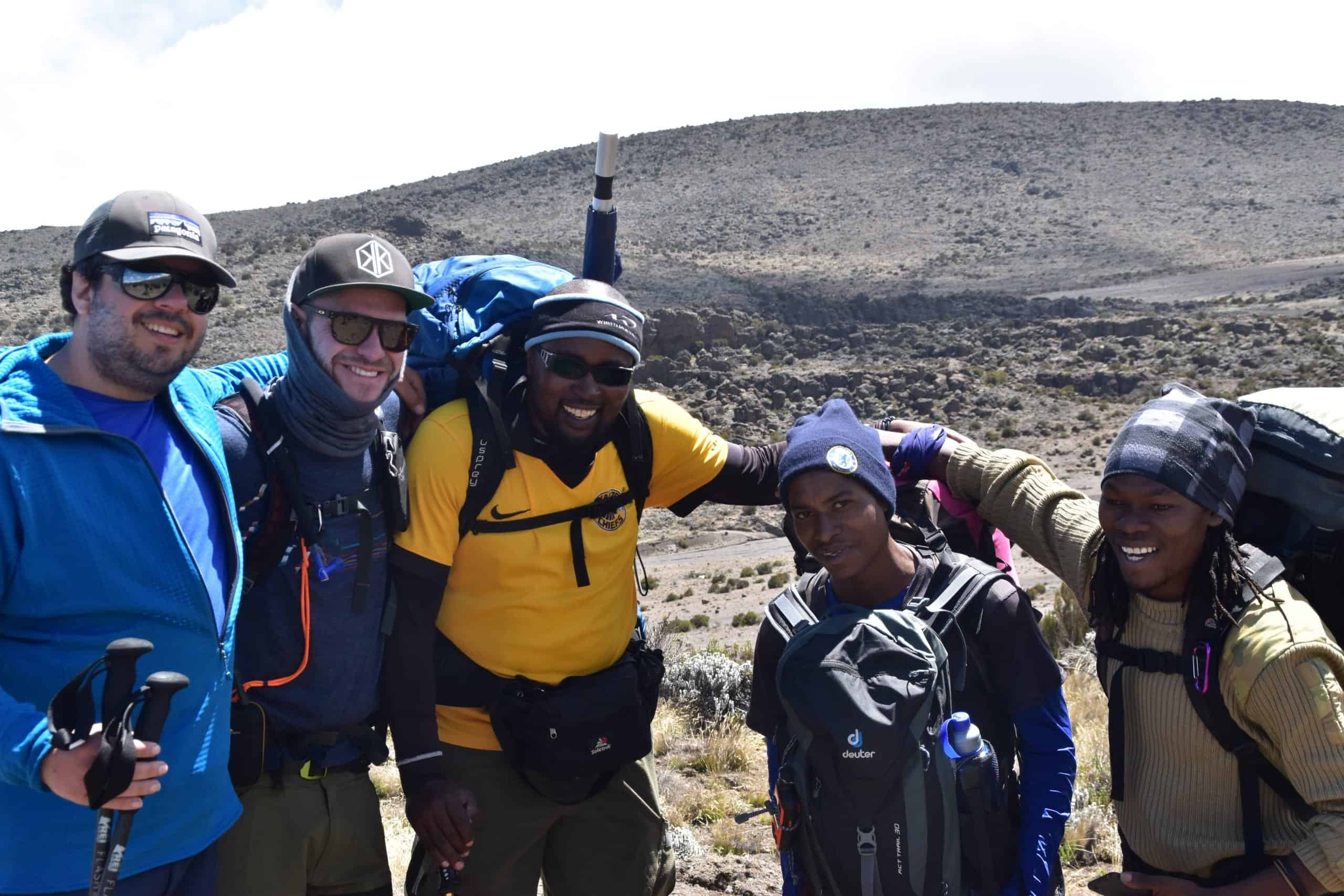 Two trekkers and three mountain crew, including chief guide Joshua Ruhimbi and assistant guide Ibrahim, pose for the camera with the desert slopes of Kibo behind, near Third Cave Campsite