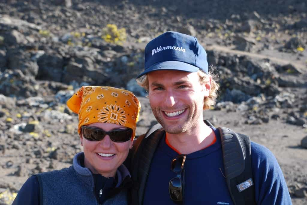 Two trekkers, lady in bandanna, map in cap, smiling on Kilimanjaro