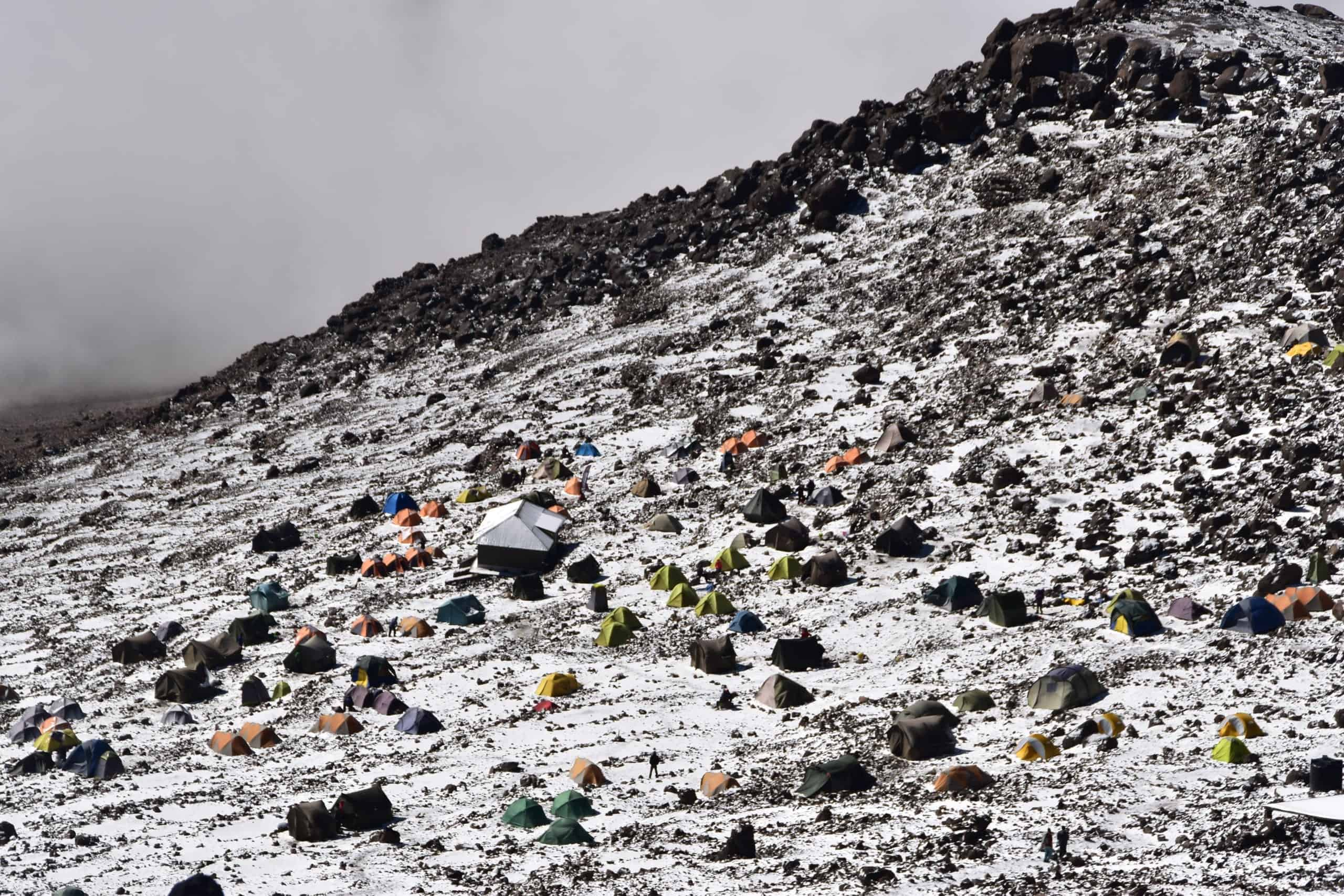 Kilimanjaro's rocky, chilly Barafu Campsite, with tents dotted here and there and the ranger's hut in the middle, as seen from the trail above, with snow dusting the ground.